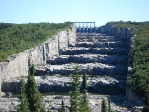 spillway: a passageway through which surplus water escapes from a reservoir, lake, or the like.  (wikimedia)