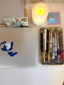 corner of desk with pens, flameless candle, and totems
