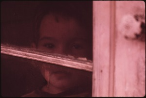 MULKY_SQUARE_CHILD_LOOKS_OUT_OF_SCREEN_DOOR_ON_A_RAINY_DAY_HIS_FAMILY_OCCUPIES_PART_OF_A_BUILDING_THAT_WILL_SOON_BE..._-_NARA_-_553554